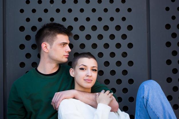 若い男の短い髪のガールフレンドの首を抱きしめる