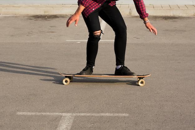 アスファルトの上のロングボードに乗ってスケーター
