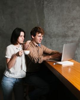 若いカップルがラップトップに取り組んで
