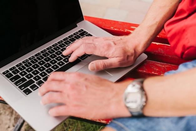 Вид сбоку руки на клавиатуре ноутбука