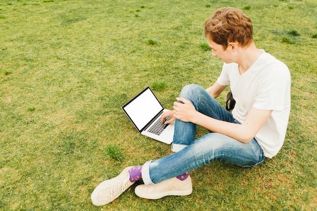 若い男が緑の芝生にラップトップを使用して