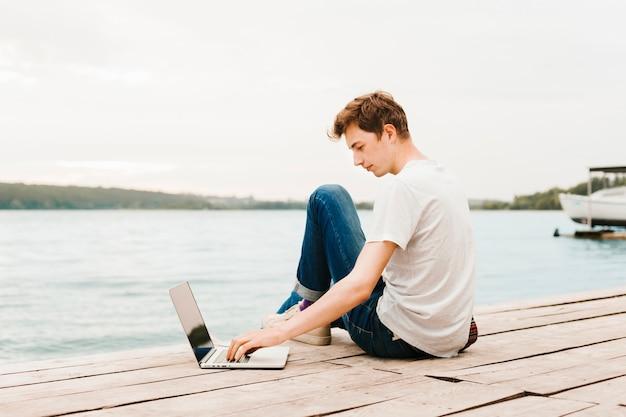 Молодой человек работает на ноутбуке у озера