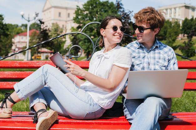 公園でお互いを見ている若いカップル