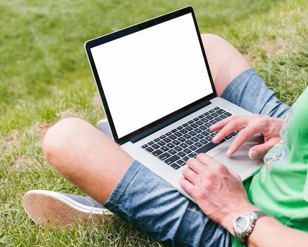 Мужчина держит ноутбук в парке