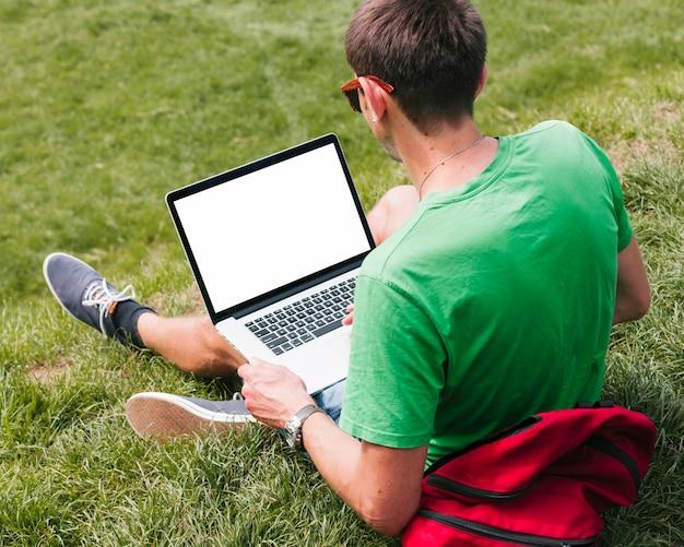 Человек сидит на траве и держит ноутбук