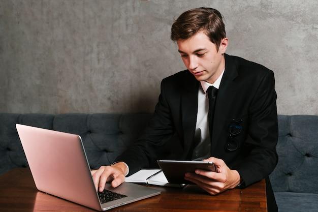 Молодой человек в офисе работает на ноутбуке