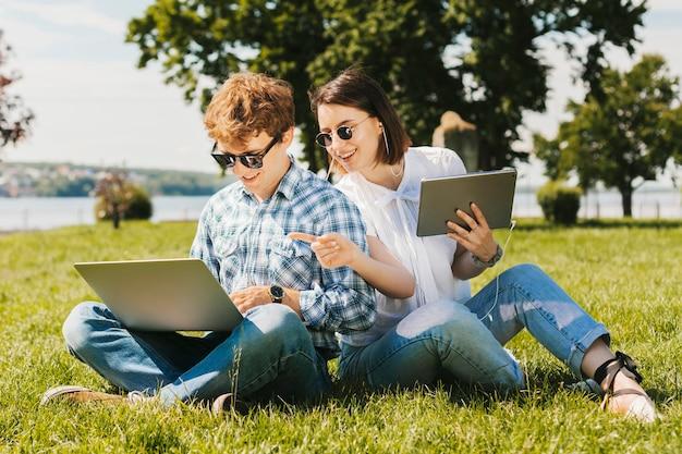 公園で働く若いフリーランスカップル