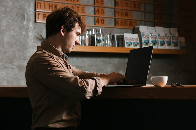 横顔の男がオフィスでラップトップに取り組んで