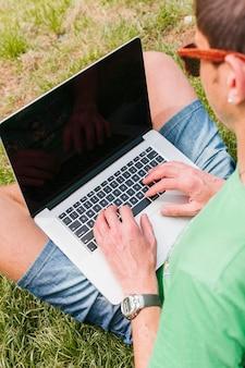 Цветочная мужчина работает на ноутбуке в парке