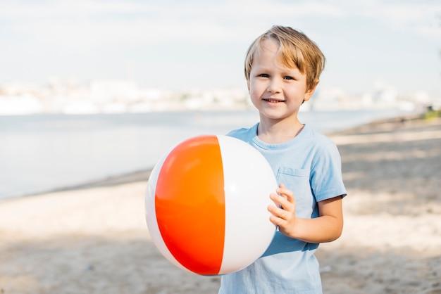 Улыбающийся мальчик, перевозящих пляжный мяч