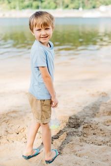 ゴーグルを運ぶ少年はビーチで好転します。