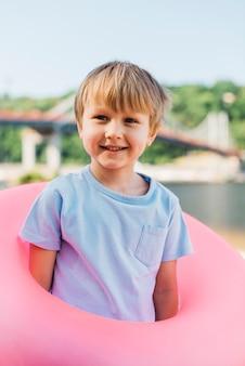 遊び心のある少年が岸に水泳リングで立っています。