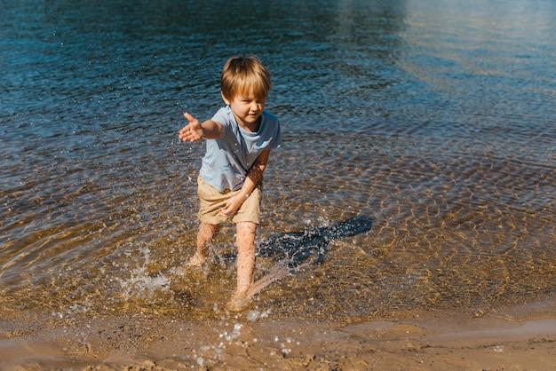 Маленький ребенок брызг воды на пляже