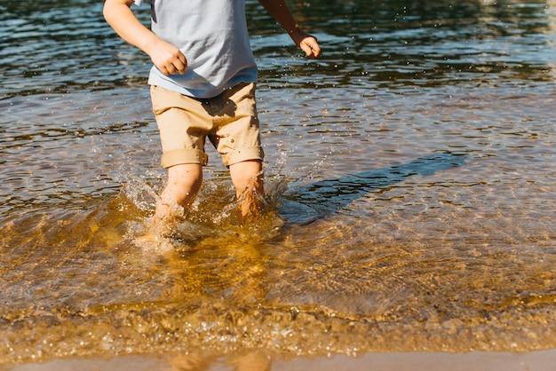Маленький мальчик плещется в воде
