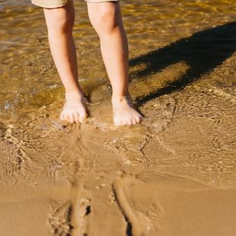 ビーチで水に子供の足
