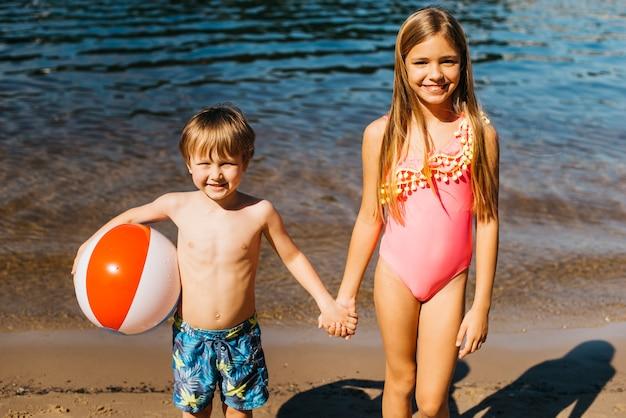 ビーチで手を繋いでいる子供たちの笑顔