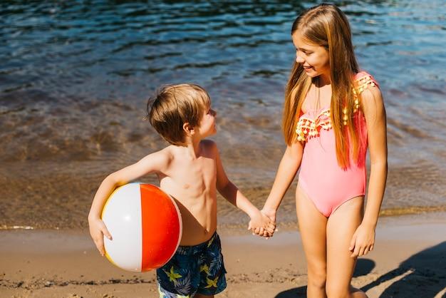 海岸でお互いを見て元気な子供たち