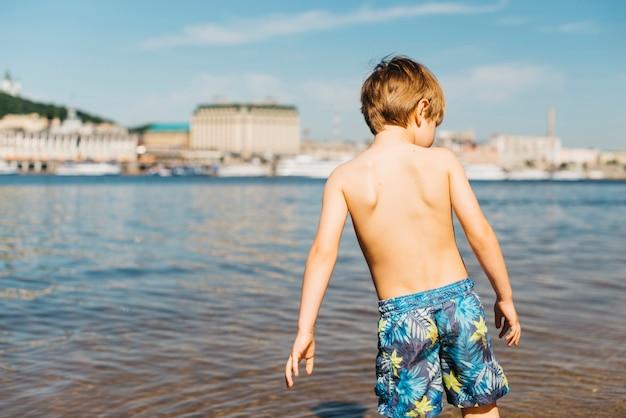 川に入ってくる小さな男の子