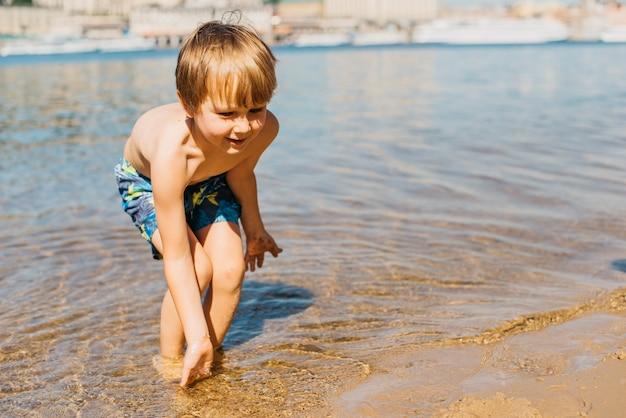 Маленький ребенок играет в море
