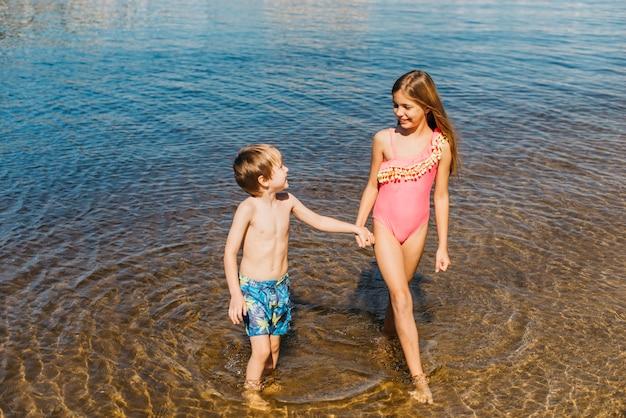 幸せな子供たちがビーチに水に立っています。