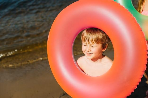 Маленький ребенок держит надувное плавательное кольцо