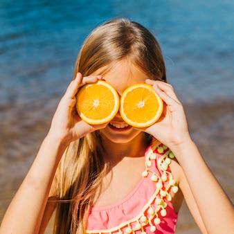 小さな女の子がビーチでオレンジ色で遊んで