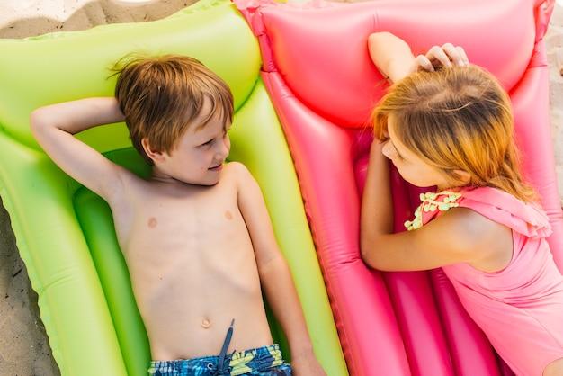 小さな子供たちはビーチでエアマットレスでリラックス