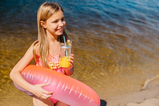 海岸に明るい水泳リングで興奮している女の子