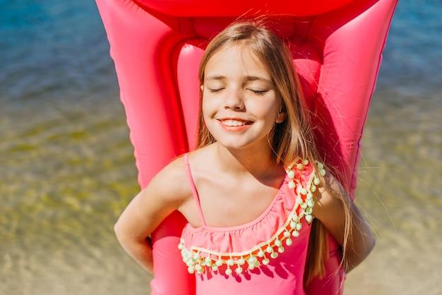Улыбающаяся девушка держит надувной матрас стоя у воды