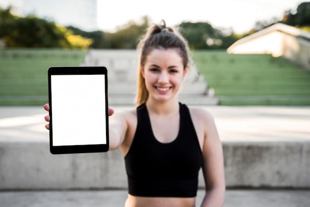 Молодая женщина держит планшет