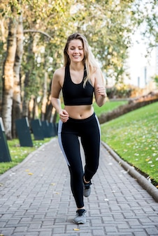 Молодая женщина работает на открытом воздухе с спортивной одежды
