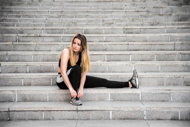 Молодая женщина, связывая ее кроссовки