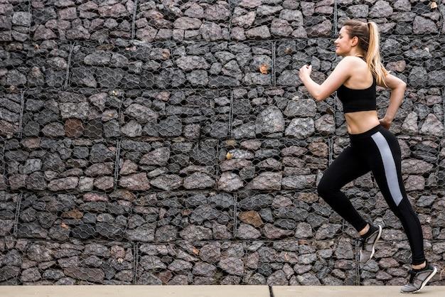 スポーツウェアと屋外で走っている若い女性