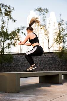 Молодая женщина делает упражнения на улице