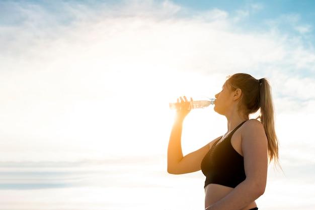 Молодая женщина пьет воду из бутылки