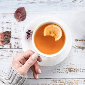 ぼろぼろの表面にお茶のカップを保持している作物女性