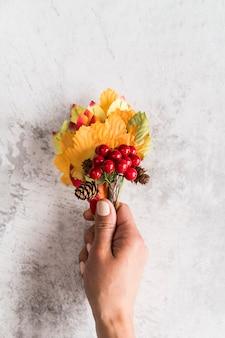 ぼろぼろの表面に秋の花束を保持している作物女性