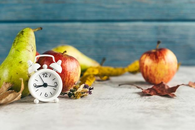 目覚まし時計の近くのリンゴとナシ