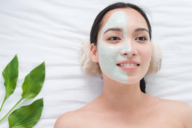 スパで顔のマスクを持つ女性