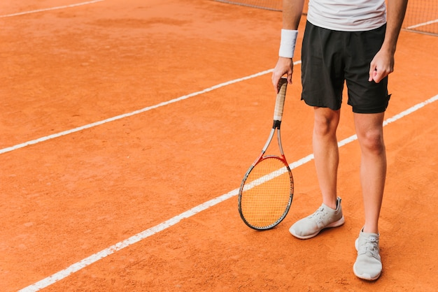 Атлетик молодой теннисист позирует