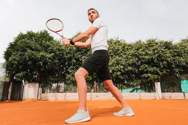 Атлетик мальчик играет в теннис