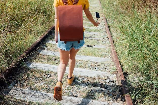 Женщина, прогуливаясь по железной дороге