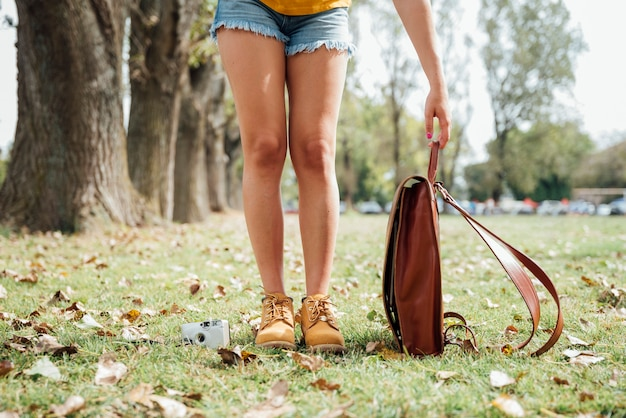 Вид спереди женщины с ее камерой и сумкой