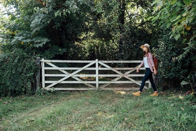 Боковой снимок женщины, проходящей мимо ворот