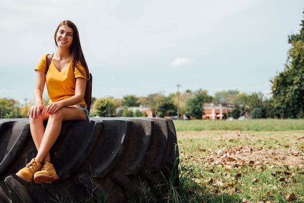トラクターの車輪の上に座っている女性の正面図