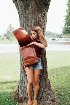 Молодая девушка смотрит в свой рюкзак