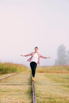 Молодая девушка балансирует на железной дороге