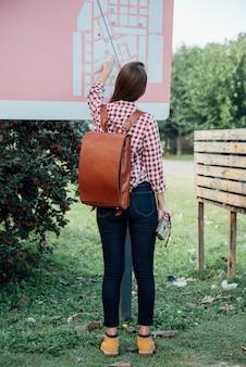 Вид сзади молодая девушка, проверка карты в парке