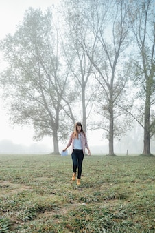 Полная съемка молодая девушка гуляет в парке