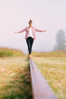 Низкий угол молодая девушка, балансируя на железной дороге